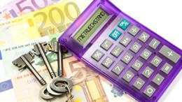 Euro-Banknoten, Hausschlüssel und einen Taschenrechner für rückständige Miete