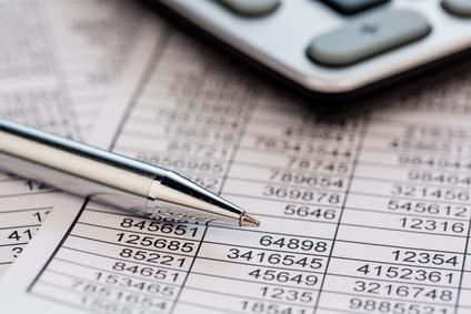 Ein Taschenrechner liegt auf den Zahlen einer Bilanz uns Statistik. Symbolphoto für Umsatz, Gewinn und Kosten.