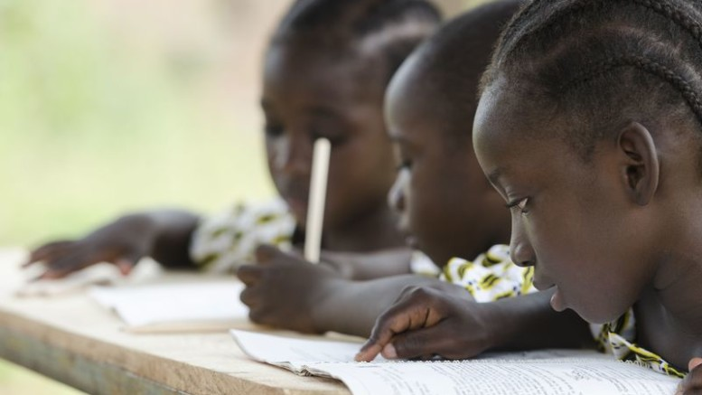 Two beautiful African girls and one African boy reading and writing at school as an educational symbol outside their school in Bamako, Mali. Beautiful education symbol background.