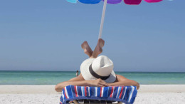 Eine Frau mit Sonnenhut liegt unter einem bunten Schirm am Strand