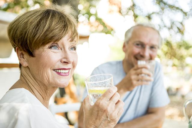 Frau und Mann mit Wasserglaesern