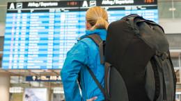Frau am Flughafen vor Anzeigetafel - ERGO Reiseversicherung Verbraucherinformation