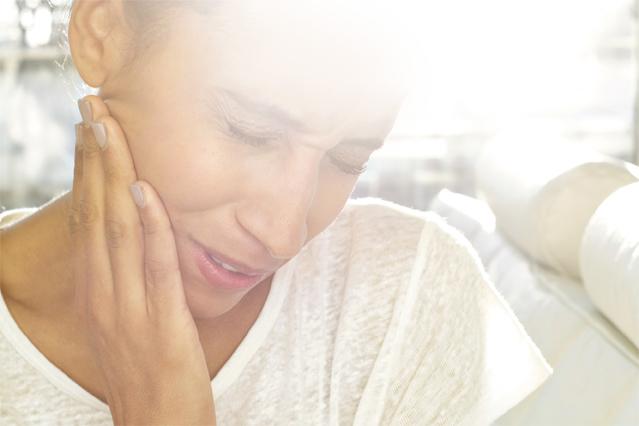 Frau fasst sich an die schmerzhafte Backe