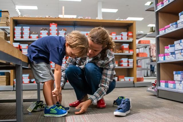 Frau mit Kind beim Anprobieren von Schuhen