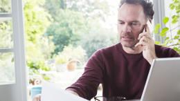 Mann mit Handy am Ohr vor Laptop