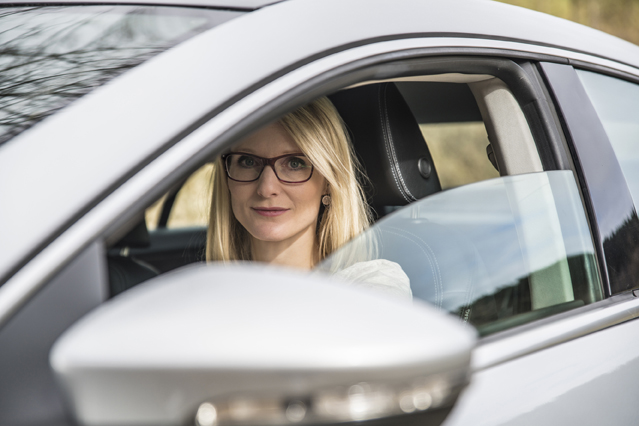 Frau mit Brille sitzt am Steuer