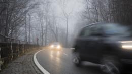 Zwei Autos in der Kurve bei Nebel