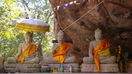 Drei Buddhas vor einem Tempel
