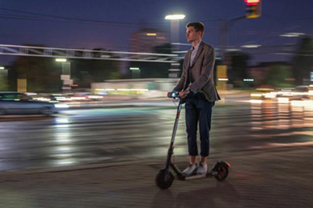 Mann im Businesslook faehrt am Abend mit E-Scooter schnell auf dem Buergersteig.