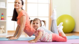 Mother and child daughter doing yoga exercises on floor in the room at home. Family having fun indoors with fitness.