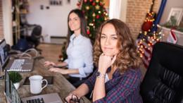 Zwei Frauen sitzen in weihnachtlichem Buero