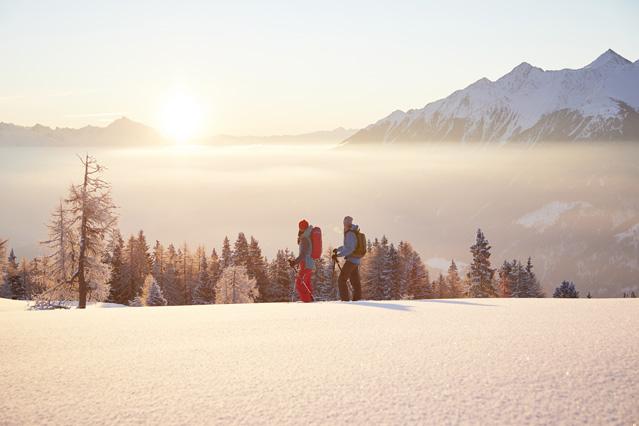 Schneeschuhwanderer bei Sonnenaufgang
