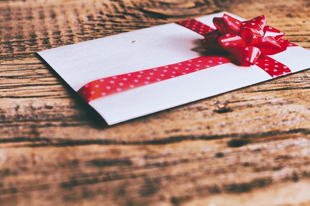 Briefumschlag mit Schleife auf Tisch
