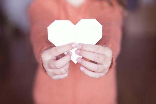 Ein Mädchen hält ein gebasteltes Herz aus Papier in den Händen