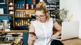 Fraus sitzt am Handy blickend und Laptop am Tisch im Café
