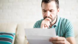 Mann schaut kritisch einen Brief an