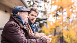 Jüngerer und älterer Herr unterhalten sich im Herbst auf einem Balkon
