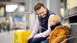 Vater sitzt mit Sohn am Bahnsteig