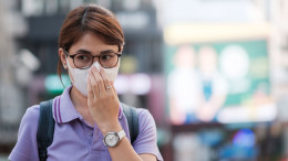 young Asian woman wearing protection mask against flu virus in the city. healthcare and air pollution concept