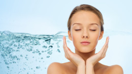 beauty, people, moisturizing, skin care and health concept - young woman face and hands over water splash background