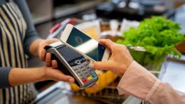Frau zahlt im Supermarkt an der Kasse mit ihrem Smartphone