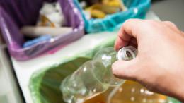 Hand wirft leere Plastikflasche in den Muelleimer