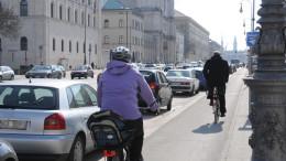 Frau mit Helm faehrt auf dem Radweg Fahrrad
