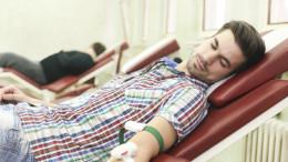 Junger Mann auf einer Liege beim Blutspenden