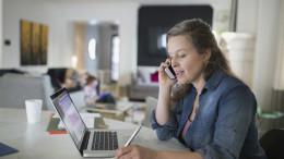 Frau telefoniert vor Laptop mit Kalender