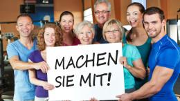 """Große lachende Gruppe hält ein """"Machen sie mit"""" Schild im Fitnesscenter"""
