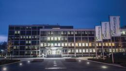 Blaue Stunde, abends, Haupteingang, Licht im Buero, Springbrunnen, Parkplatz, Fahnen