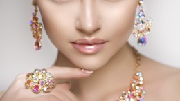 Beautiful woman in a necklace, earrings and ring. Model in jewelry from precious stones, diamonds.