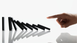 Businessman Touching Domino Pieces Arranged in a Line --- Image by © Royalty-Free/Corbis