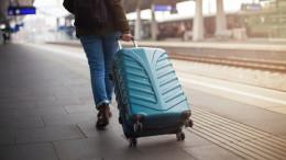 Reisender mit Koffer geht den Bahnsteig entlang