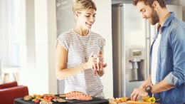 Happy young couple preparing food together in kitchen. Woman is holding coffee cup while man cutting carrots at kitchen island. They are in casuals at home.
