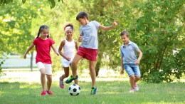 Cute children playing football in park