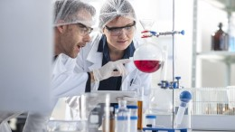 Two scientists working in lab together looking at flask