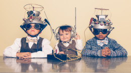A young boy imagines reading minds of his two friends with a homemade science project. They are dressed in casual clothing, glasses and bow ties. They are serious and sitting at a table with helmets on their heads in front of a beige background. Retro styling.