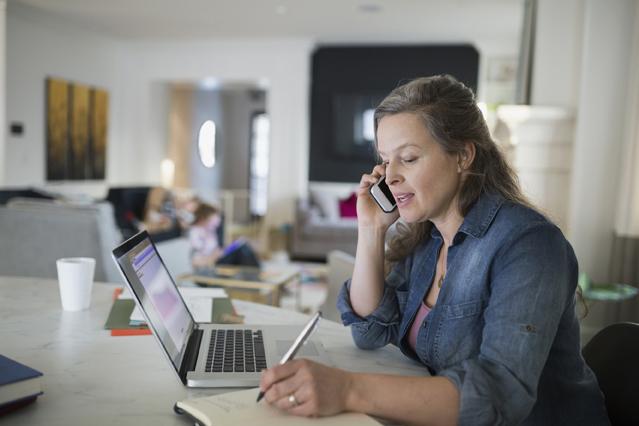 Mutter telefoniert und überprüft ihren Terminplaner am Schreibtisch