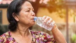 The elderly asian woman drinking water from bottle in park