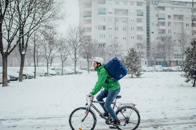 Mann fährt bei Schnee auf dem Fahrrad