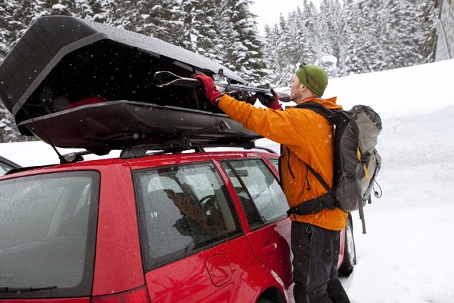 Mann laedt Skiier in Dachbox