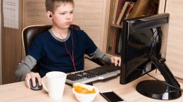 Boy eating potatoes chips and surfing on internet or playing video games on PS. Kid in headphones eating chips while using pc in his room.