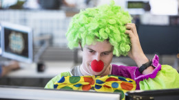 Mann als Clown verkleidet am Arbeitsplatz