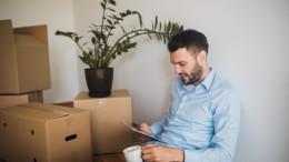Ein Mann lehnt neben Umzugskartons an der Wand und schaut auf sein iPad