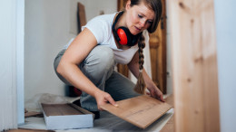 Eine Frau renoviert den Wohnungsboden
