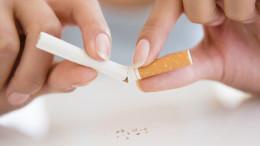 Eine Frau bricht eine Zigarette durch