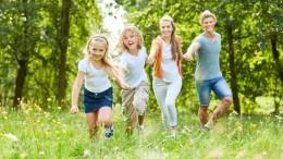 Glückliche Familie und Kinder haben Spaß im Garten im Sommer