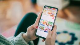 Junge Frau betrachtet Gerichte eines Lieferdienstes auf ihrem Smartphone