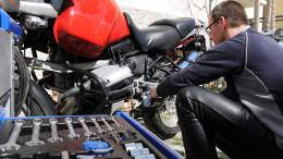 Ein Mann repariert etwas an seinem Motorrad